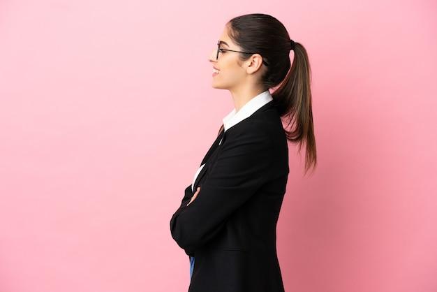 Jovem mulher de negócios caucasiana isolada em um fundo rosa na posição lateral