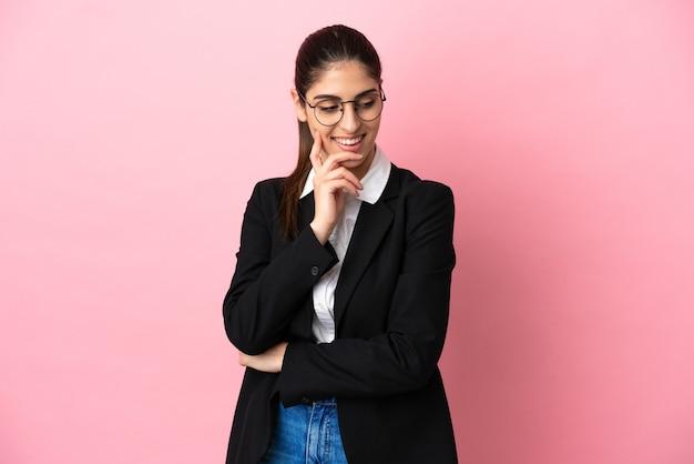 Jovem mulher de negócios caucasiana isolada em um fundo rosa olhando para o lado