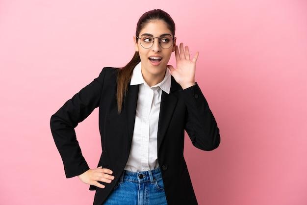 Jovem mulher de negócios caucasiana isolada em um fundo rosa ouvindo algo colocando a mão na orelha