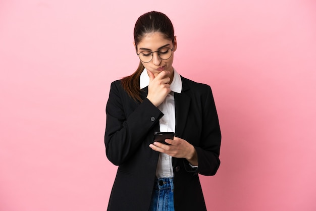Jovem mulher de negócios caucasiana isolada em um fundo rosa pensando e enviando uma mensagem