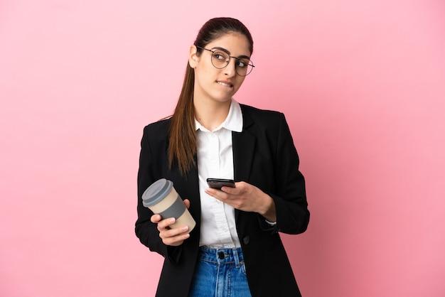 Jovem mulher de negócios caucasiana isolada em um fundo rosa segurando um café para levar e um celular enquanto pensava em algo