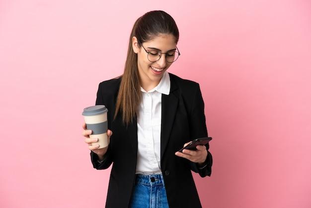 Jovem mulher de negócios caucasiana isolada em um fundo rosa segurando um café para levar e um celular