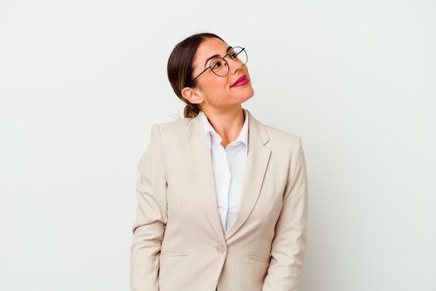 Jovem mulher de negócios, caucasiana, isolada no fundo branco, sonhando em alcançar objetivos e propósitos.
