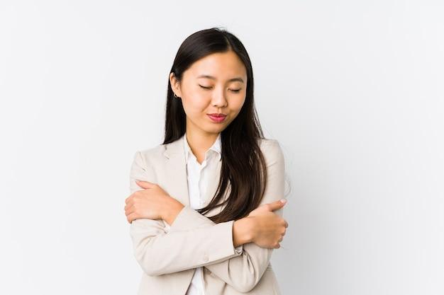 Jovem mulher de negócios chinesa isolada abraços, sorrindo despreocupada e feliz