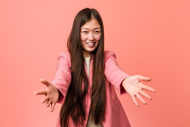 Jovem mulher de negócios chinesa vestindo um terno rosa e se sentindo confiante para dar um abraço