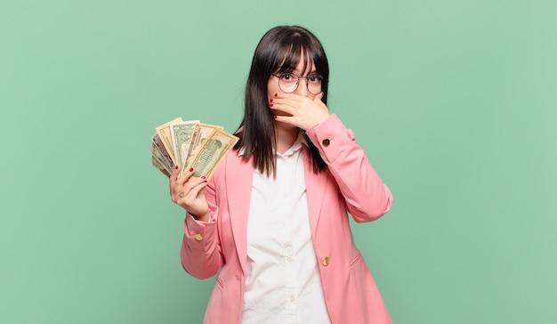 Jovem mulher de negócios cobrindo a boca com as mãos com uma expressão chocada e surpresa, mantendo um segredo ou dizendo oops