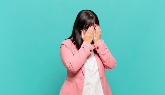 Jovem mulher de negócios cobrindo os olhos com as mãos com uma expressão triste e frustrada de desespero, chorando, vista lateral