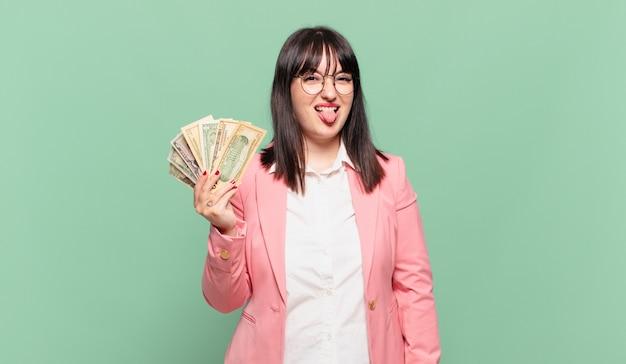 Jovem mulher de negócios com atitude alegre, despreocupada e rebelde, brincando e mostrando a língua, se divertindo