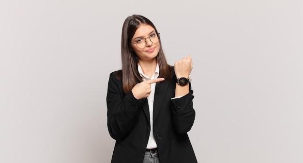 Jovem mulher de negócios com cara de impaciente e zangada, apontando para o relógio, pedindo pontualidade, quer ser pontual