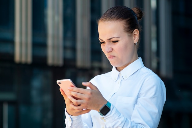 Jovem mulher de negócios com nojo carrancuda com raiva surfando smartphone na antipatia