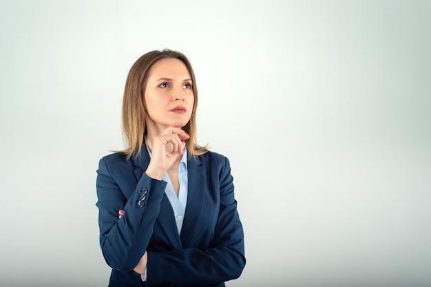 Jovem mulher de negócios com olhar distante isolado em fundo cinza