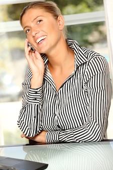 Jovem mulher de negócios com telefone celular e laptop