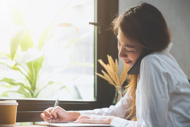 Jovem mulher de negócios com vestido branco sentado à mesa no café e escrevendo no caderno