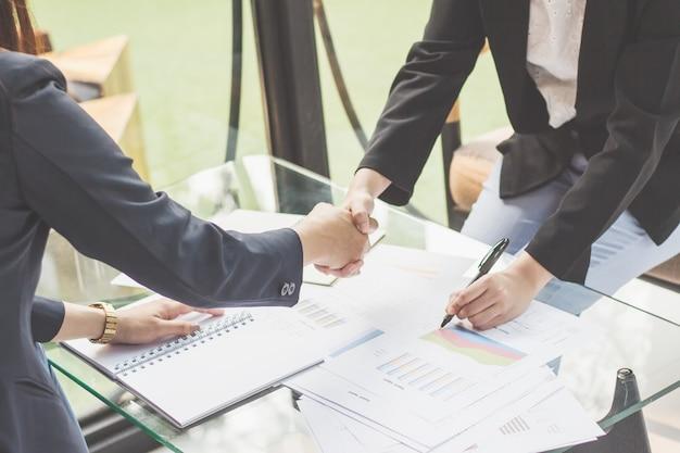 Jovem mulher de negócios concorda em ser parceiro, gerente de vendas estão apresentando itens de exportação para parte