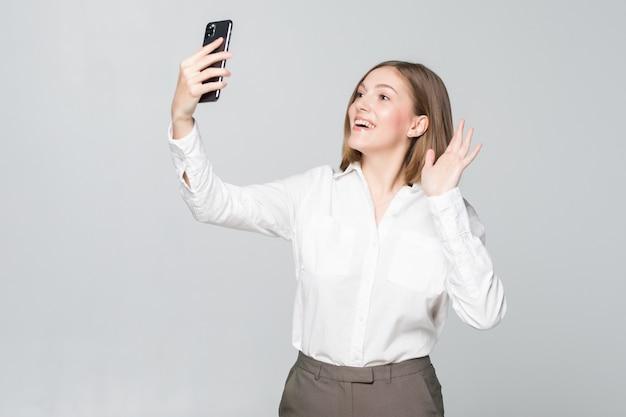 Jovem mulher de negócios cumprimentando alguém em videochamada no telefone