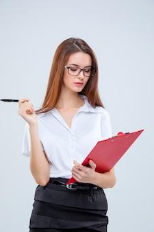 Jovem mulher de negócios de óculos com caneta e prancheta