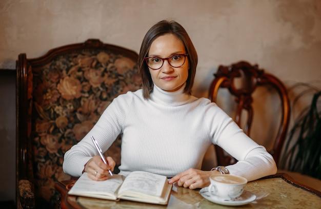 Jovem mulher de negócios de óculos com um suéter branco sentada a uma mesa com café