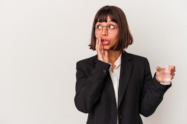 Jovem mulher de negócios de raça mista segurando um copo de água isolado no fundo branco está contando uma notícia secreta de travagem e olhando para o lado