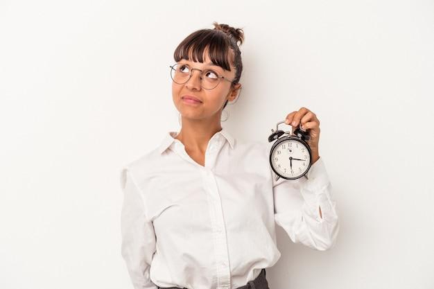 Jovem mulher de negócios de raça mista segurando um despertador isolado no fundo branco e sonhando em alcançar objetivos e propósitos