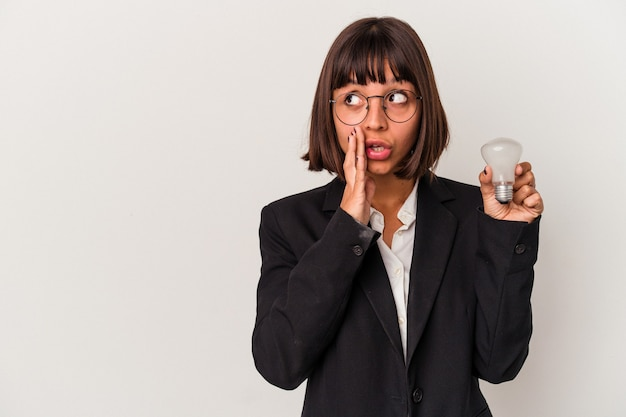 Jovem mulher de negócios de raça mista segurando uma lâmpada isolada no fundo branco e contando uma notícia secreta de travagem e olhando para o lado