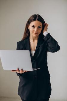 Jovem mulher de negócios em pé com o laptop no escritório