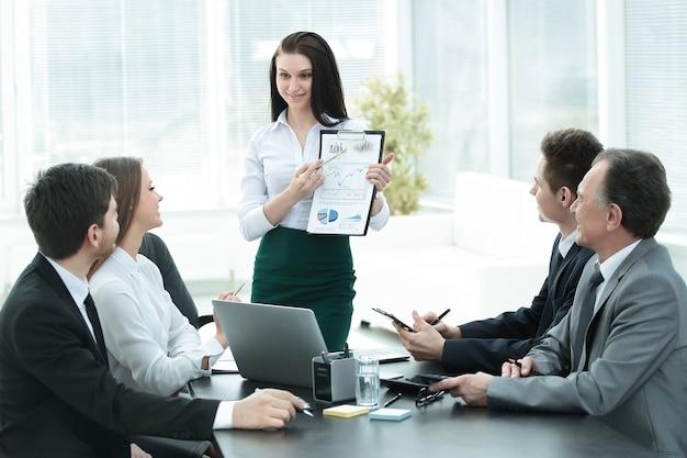 Jovem mulher de negócios em reunião de negócios com a equipe de negócios