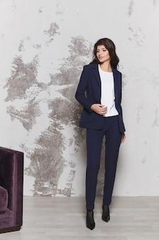 Jovem mulher de negócios em um elegante terno azul e blusa branca conceito de moda empresarial