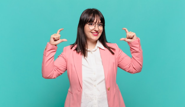 Jovem mulher de negócios emoldurando ou delineando seu próprio sorriso com as duas mãos, parecendo positiva e feliz, conceito de bem-estar
