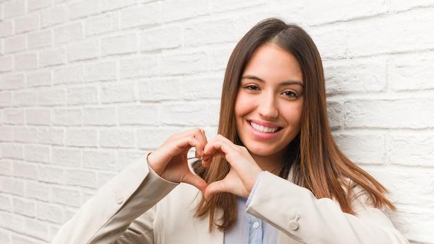 Jovem mulher de negócios, fazendo uma forma de coração com as mãos