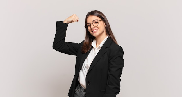 Jovem mulher de negócios feliz, satisfeita e poderosa, flexionando a forma e bíceps musculosos, parecendo forte depois da academia