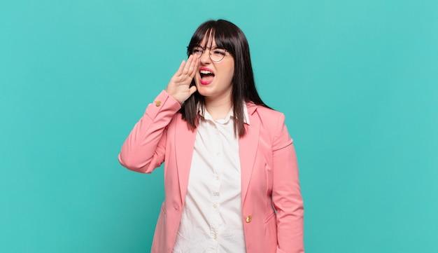 Jovem mulher de negócios gritando bem alto e com raiva para copiar o espaço ao lado, com a mão perto da boca