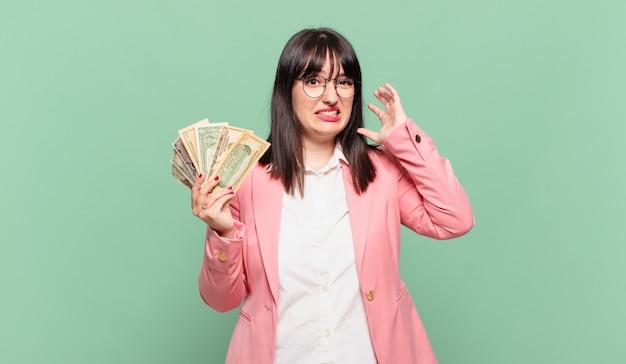 Jovem mulher de negócios gritando com as mãos para o alto, sentindo-se furiosa, frustrada, estressada e chateada