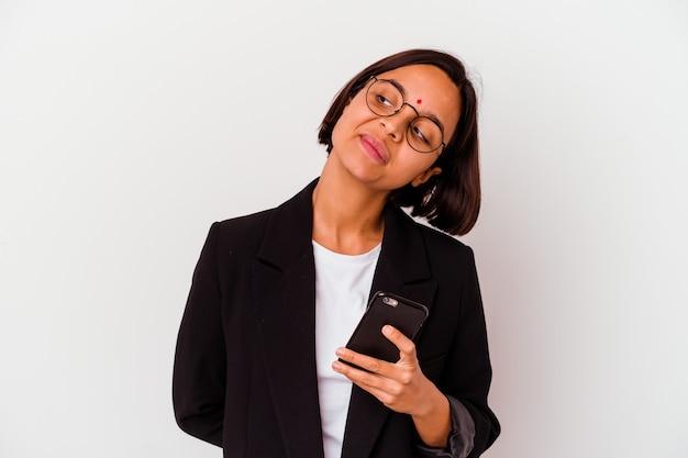 Jovem mulher de negócios indiana segurando um telefone isolado, sonhando em alcançar objetivos e propósitos