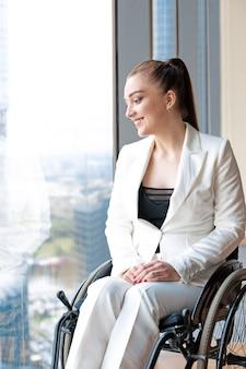 Jovem mulher de negócios inválida ou com deficiência sentada em cadeira de rodas no escritório