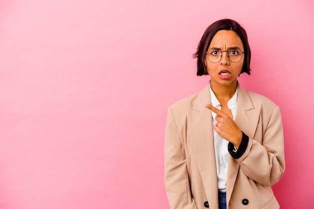 Jovem mulher de negócios isolada em uma parede rosa apontando para o lado