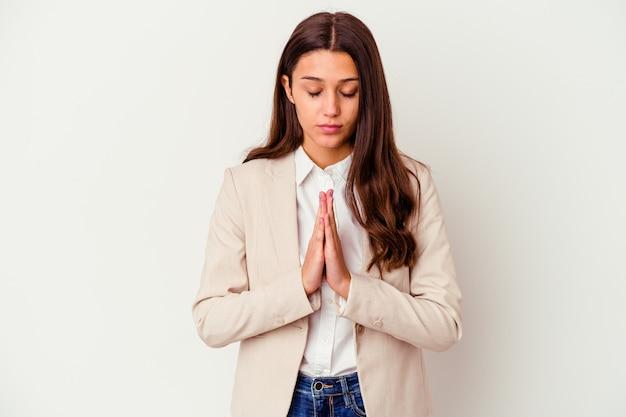 Jovem mulher de negócios isolada na parede branca, de mãos dadas para rezar perto da boca, sente-se confiante