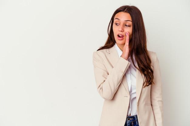 Jovem mulher de negócios isolada na parede branca dizendo uma notícia secreta sobre a travagem e olhando para o lado