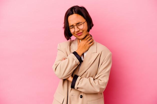 Jovem mulher de negócios isolada na parede rosa com dor de garganta devido a um vírus ou infecção