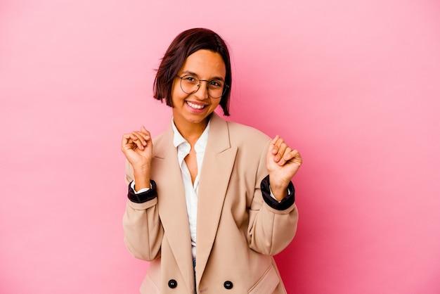 Jovem mulher de negócios isolada na parede rosa comemorando um dia especial, pula e levanta os braços com energia