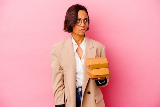 Jovem mulher de negócios isolada na parede rosa confusa, duvidosa e insegura