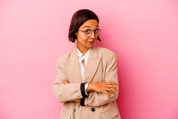 Jovem mulher de negócios isolada na parede rosa, olhando para a câmera com expressão sarcástica.