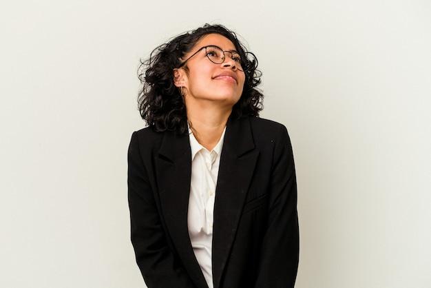 Jovem mulher de negócios latina isolada em um fundo branco, sonhando em alcançar objetivos e propósitos