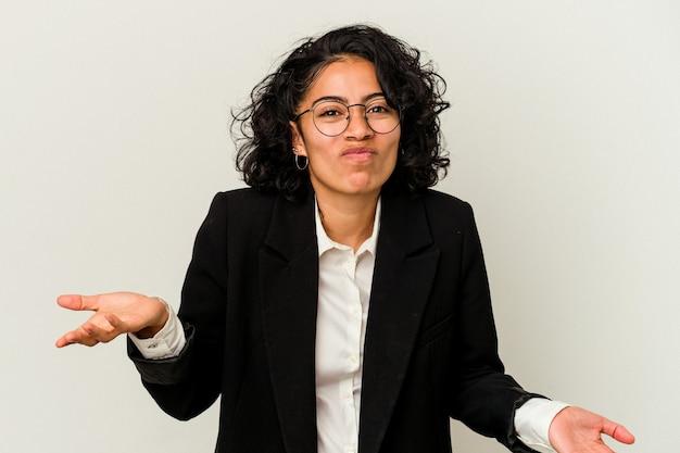 Jovem mulher de negócios latinos isolada no fundo branco encolhe os ombros e abre os olhos confusos.
