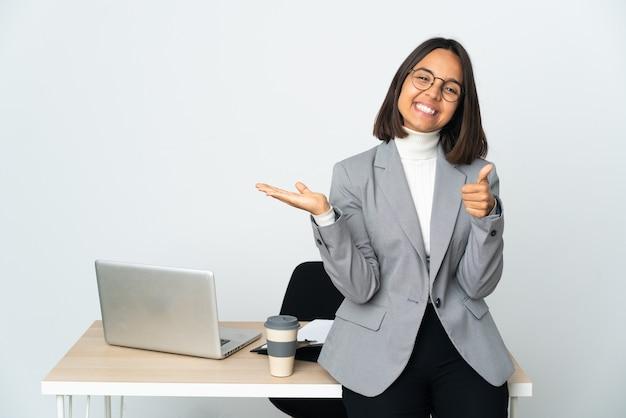Jovem mulher de negócios latinos trabalhando em um escritório isolado em uma parede branca exibindo copyspace imaginário na palma da mão para inserir um anúncio e com o polegar para cima