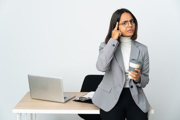 Jovem mulher de negócios latinos trabalhando em um escritório isolado na parede branca pensando em uma ideia.