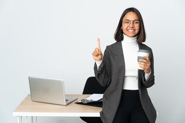 Jovem mulher de negócios latinos trabalhando em um escritório isolado no branco apontando uma ótima ideia