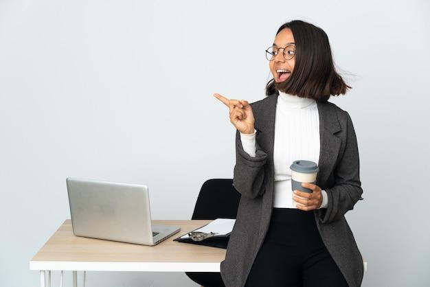 Jovem mulher de negócios latinos trabalhando em um escritório isolado no branco com a intenção de perceber a solução enquanto levanta um dedo