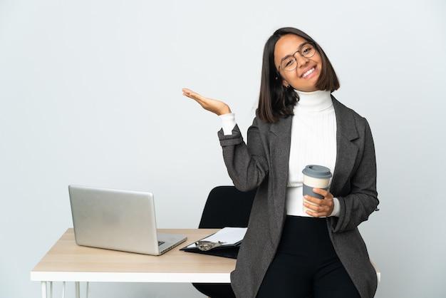 Jovem mulher de negócios latinos trabalhando em um escritório isolado no branco estendendo as mãos para o lado para convidar para vir