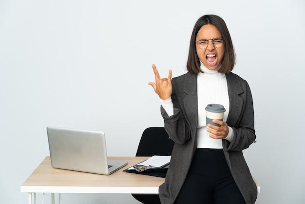 Jovem mulher de negócios latinos trabalhando em um escritório isolado no branco fazendo gesto de chifre