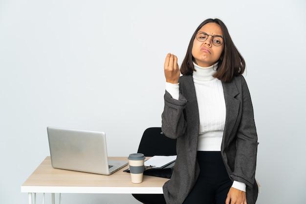 Jovem mulher de negócios latinos trabalhando em um escritório isolado no branco fazendo gestos em italiano